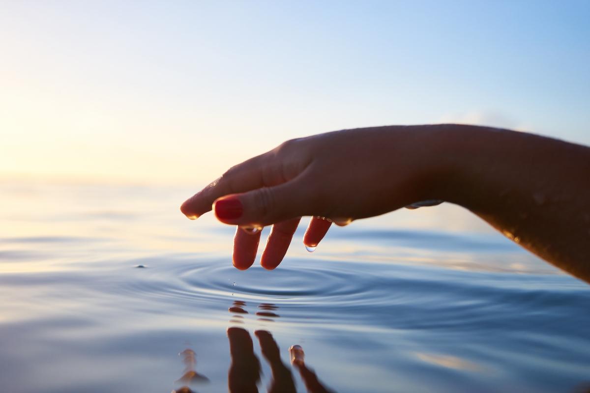 Hand berührt Wasseroberfläche – Symbolbild gute Texte schreiben mit Hilfe des Unbewussten